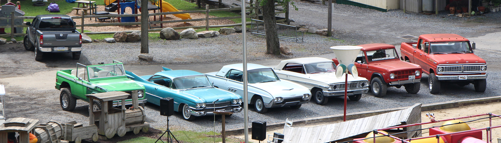 An array of classic cars parked by the playground.